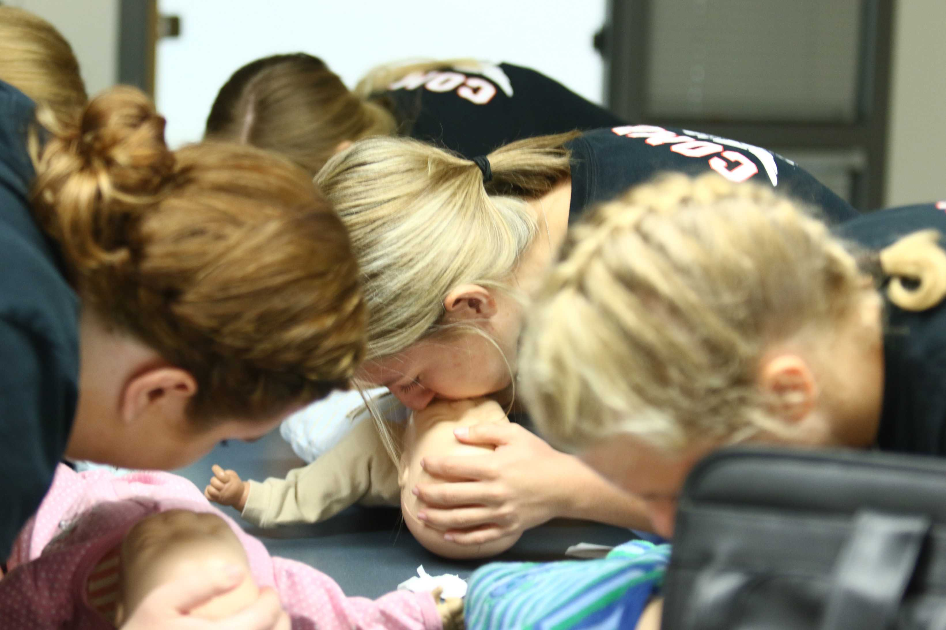 Senior, Carly Foster (middle) and other Med Profession students practice for their CPR certification.