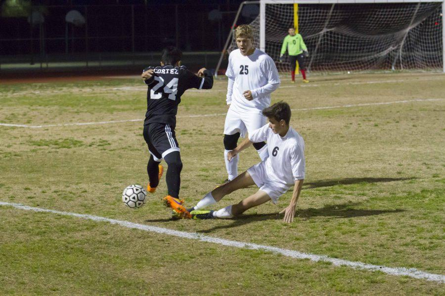 Combs Middle Fielder Doug Geng kicking the ball away from Coronado forward Irving Cazares, a strong  effort in a losing game.