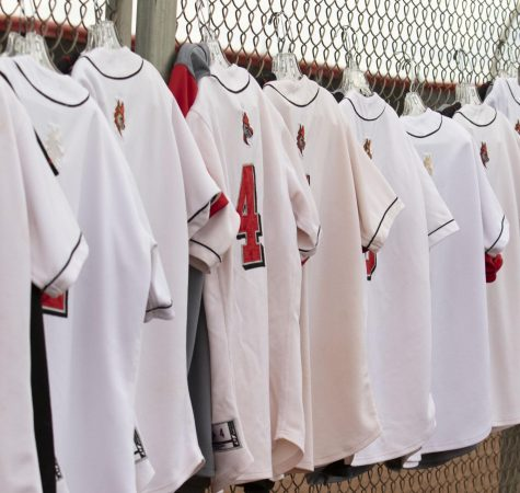 Varsity jerseys hanging from the fence.