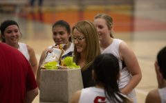Coach Mandi Webster receives her gift for becoming the third coach in school history to win 100 games.