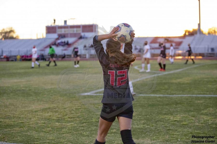 Senior defender Alexia Quinonez (12) throws the ball in during the first half of the game against the Sention Catholic Sentials on Tuesday night February 23.