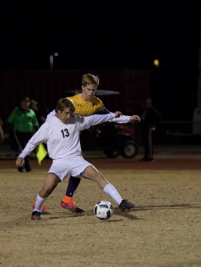 Senior defenseman Hayden Woodard steals the ball from Sunrise Mountain's Connor Froisland in the Coyotes 8-0 loss Tuesday night.