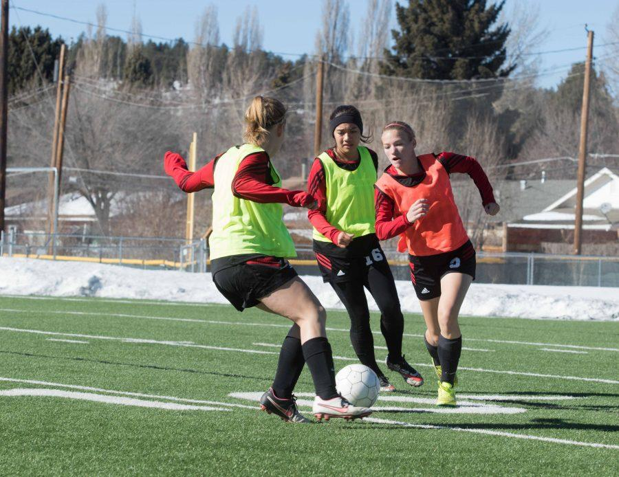 Midfielder Macey Williamson (#3), defender Vanessa Mendoza (#16) and defender Taylor Southwick warming up for the first round of state playoffs against Flagstaff High School.