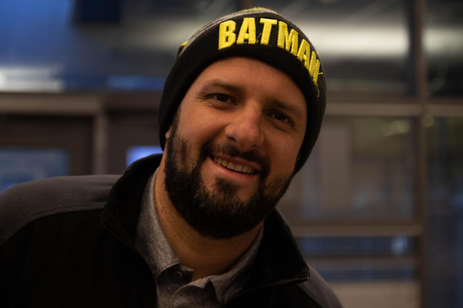 Paul Gutierrez smiling for the camera wearing a beanie of his favorite superhero.