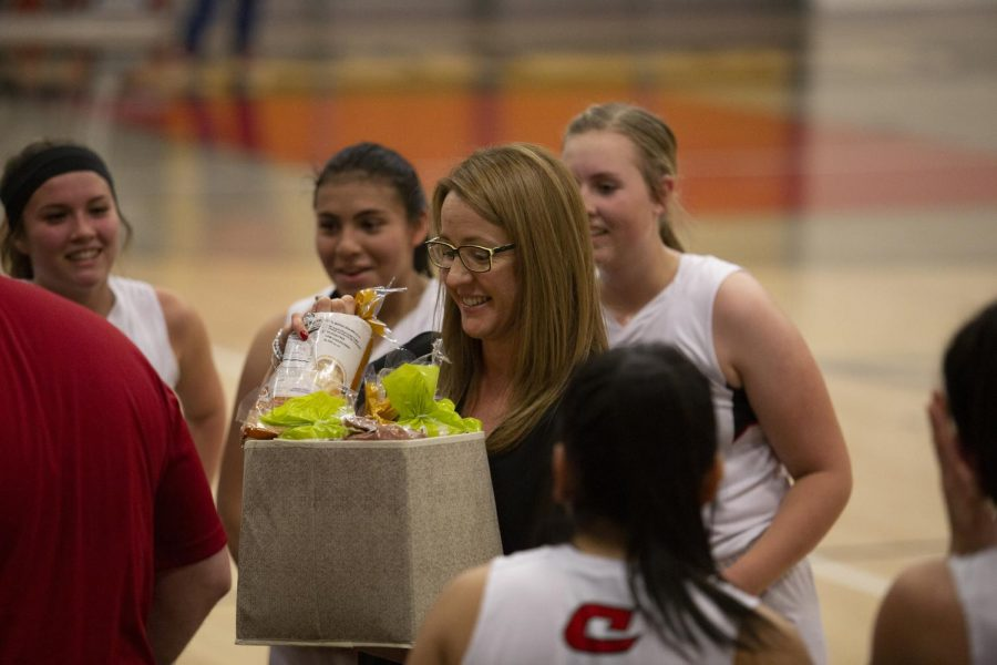Coach+Mandi+Webster+receives+her+gift+for+becoming+the+third+coach+in+school+history+to+win+100+games.
