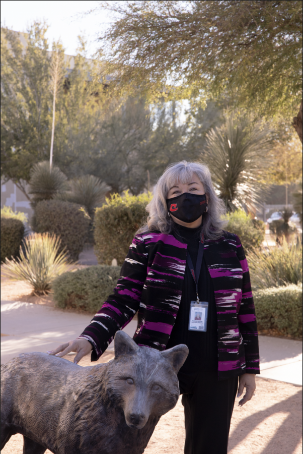 Patricia Goolsby poses with the Combs Coyote located outside the principals office.