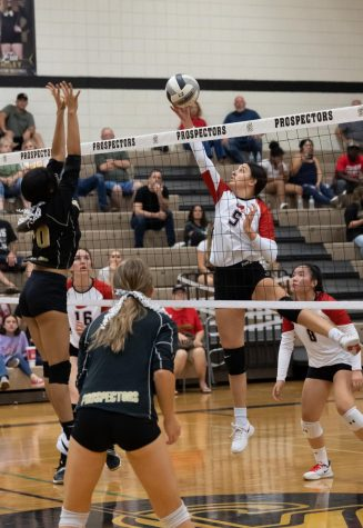 Senior middle hitter Aimee Hansen, 5, manages to reach the ball with the tips of her fingers knocking the ball back over into opponent territory.