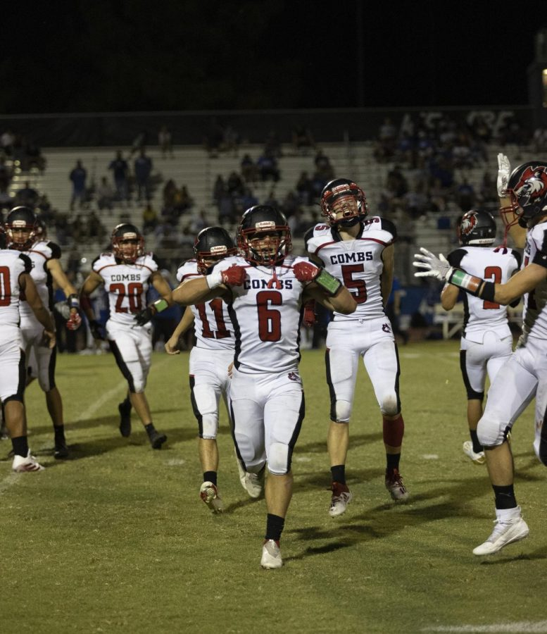 After managing to grasp an interception junior fullback Ammon Craig (6) does the superman pose as his teammates cheer him on.